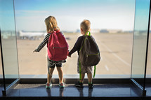 siblings holding hands looking out a window at an airport
