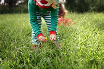 child in elf pajamas picking flowers