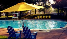 lawn chairs and umbrellas around a swimming pool