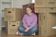 a woman sitting next to moving boxes