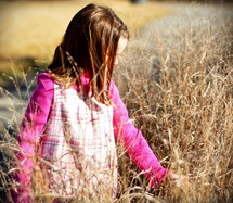 girl child walking in tall grasses