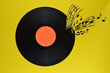 old black vinyl record with blank orange label centered on yellow background with notes and staves coming from it