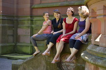 friends sitting on a stone wall ledge