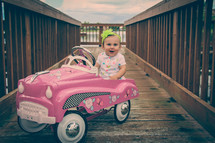 a toddler girl in a toy car