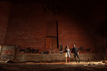 A couple holding hands in front of a warehouse