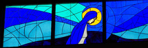 A large stained glass window mural of Mary, the mother of Jesus, praying and surrounded by a halo and shades of blue and gold.