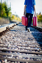 man on railroad tracks walking with luggage