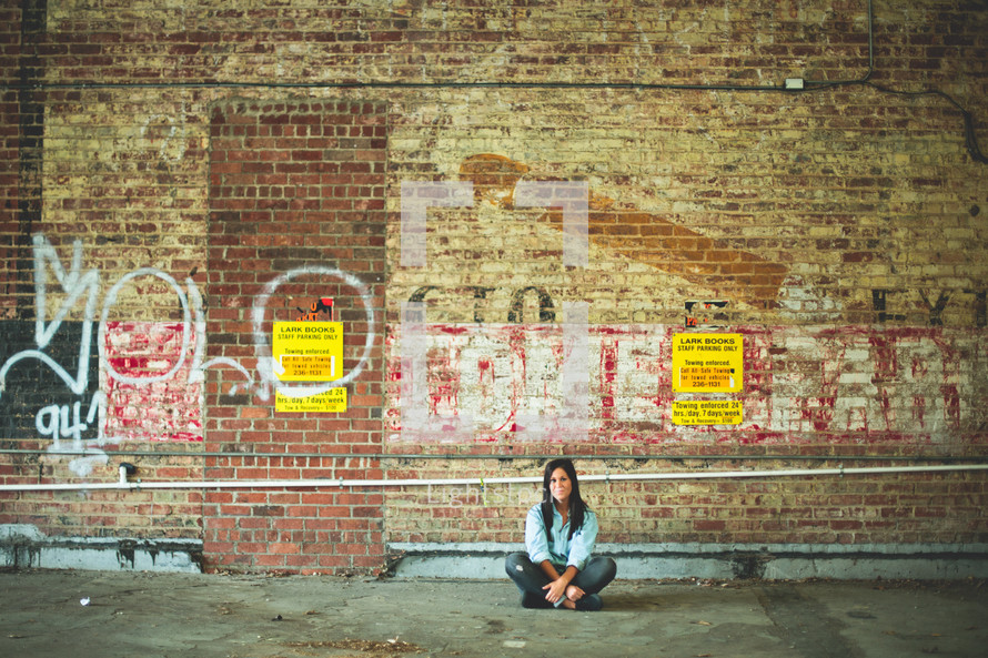 a woman sitting on the ground in front of a graffiti covered wall