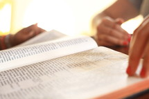 Hands on pages of Bible.