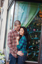 couple hugging in front of a Christmas tree in a store window