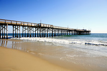 Long Pacific Ocean pier smooth sand beach crashing waves