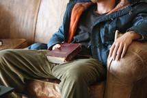Homeless man holding worn Bible