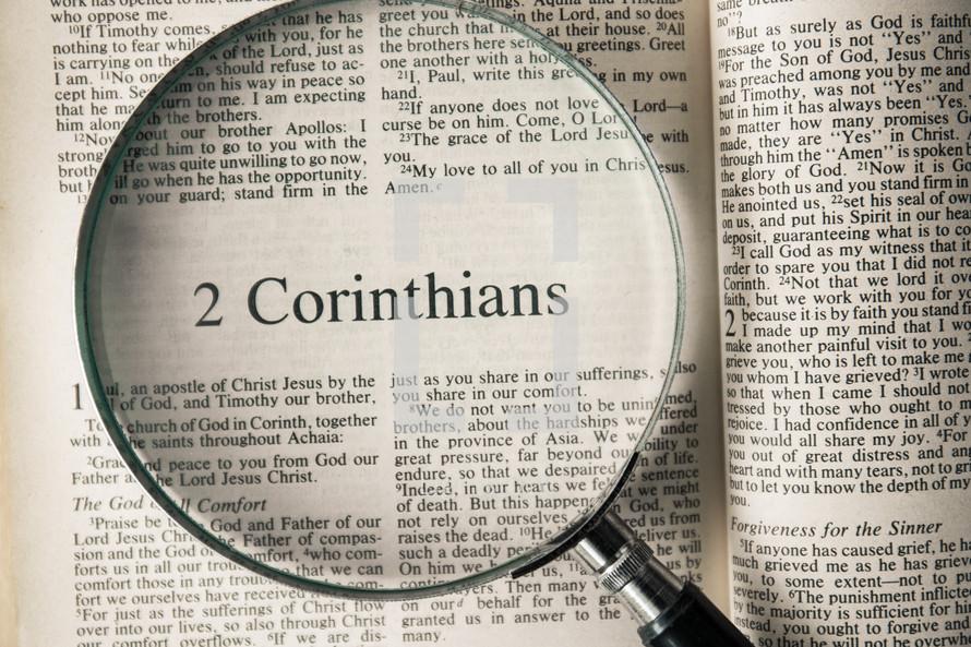magnifying glass over Bible - 2 Corinthians
