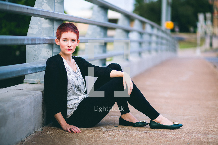 Woman sitting against the railing of an overpass.