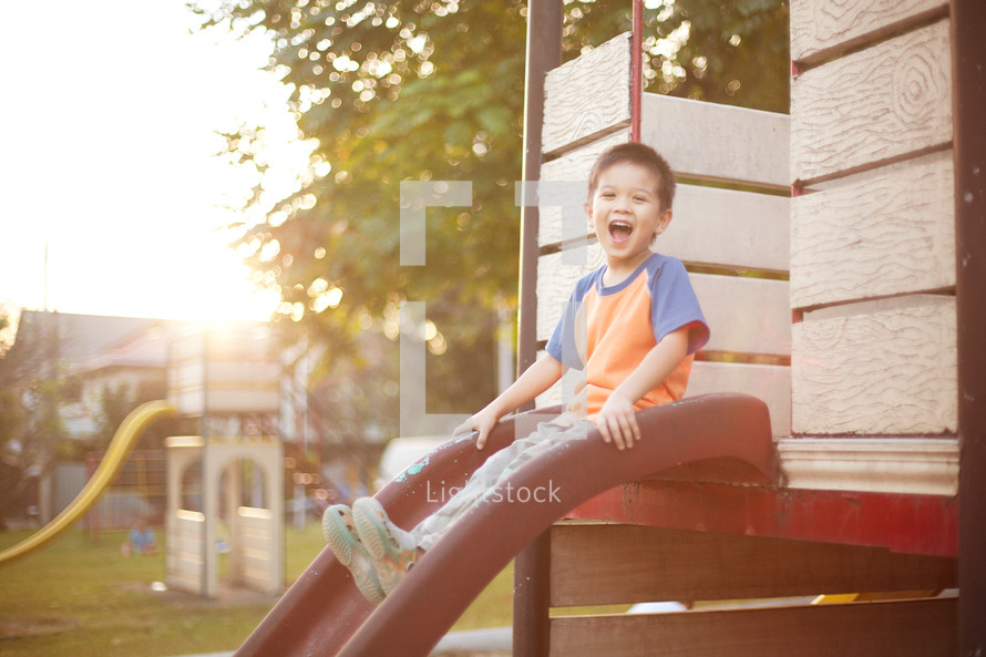 a boy child sliding down a slide on a playground