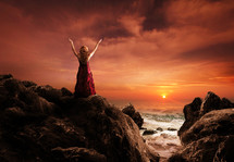 Woman standing on ocean rocks praising God at sunset.