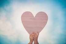 a child's hand holding up a wooden heart