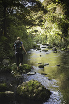 woman backpacking across moss covered rocks in a stream