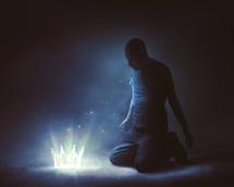 man kneeling before a glowing crown