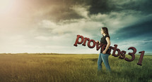 Woman carrying Proverbs 31 through a field on a stormy day.