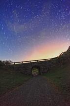 Starry night sky over a bridge.