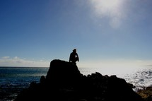 silhouette of a man crouched on a sea cliff