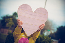 a child's hand up a wooden heart