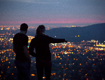 A couple standing and looking out at the lights from a suburb below