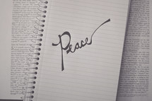 word Peace on a notebook on the pages of a Bible