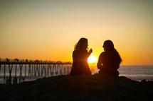 two women sitting on a beach talking