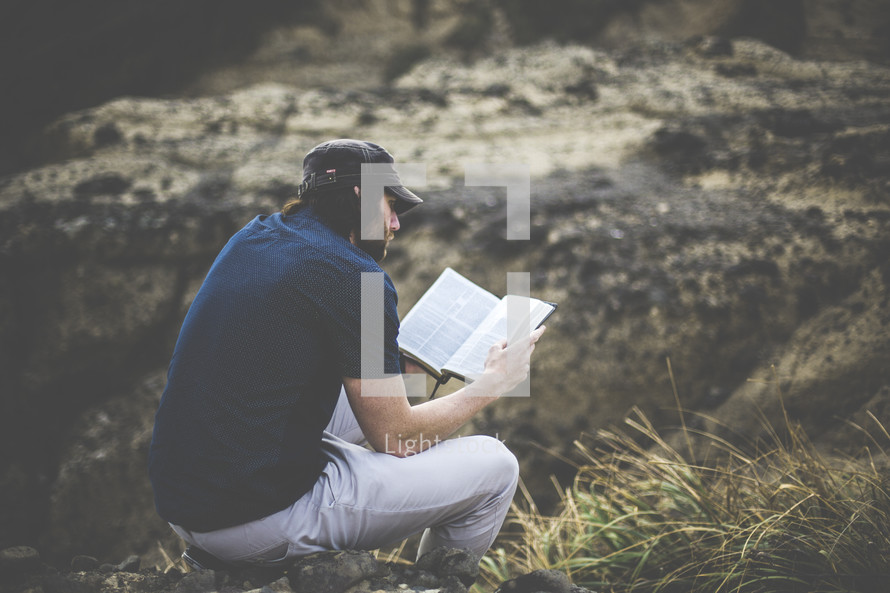 a man sitting on a rock outdoors reading a Bible
