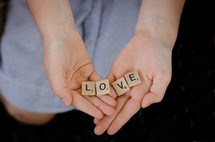 a woman holding scrabble pieces with the word love
