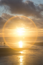 halo of sunlight and a family on a beach