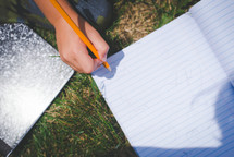boy writing in a notebook in the grass