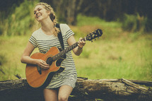 a woman playing a guitar outdoors