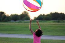 a girl child bouncing a beach ball