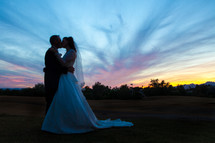 Bride and groom kissing, standing on a hillside with a sunset behind them