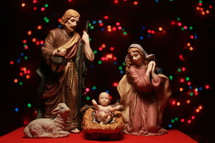 nativity with holy family and colorful bokeh lights