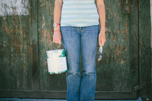 Woman standing in front of a wooden wall holding a paint can and brush
