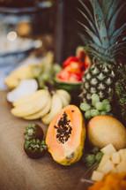 papaya, pineapple, bananas, grapes on a table