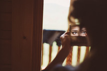 a woman looking into a mirror