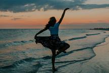 a woman dancing on a beach