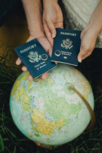 couple with wedding bands on passports and a globe