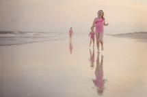 children running on wet sand at a beach