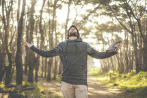 a man holding a Bible with outstretched arms looking up to God in a forest