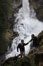 couple hiking up a mountain near a waterfall
