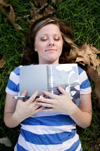 a woman lying in the grass holding a journal