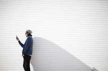 man standing in front of a white wall looking at his cellphone screen