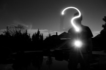 Silhouette of a teen making a question mark with a light.
