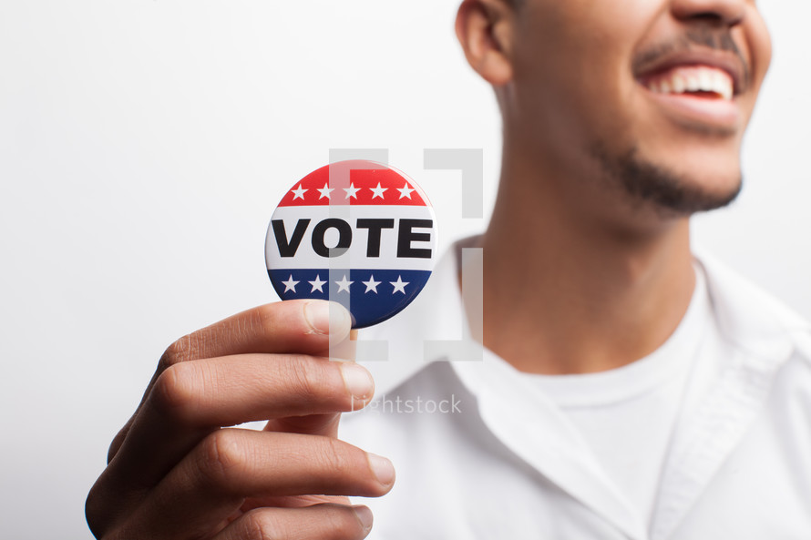 young man and vote election day buttons